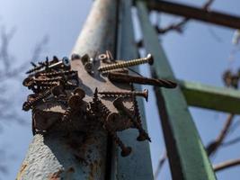 vis rouillées sur l'aimant sur le pilier de fer dans la rue contre le ciel photo