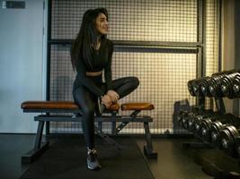 Jolie fille brune en haut noir et leggings est assise sur un banc dans une salle de tri sur une étagère avec des haltères photo