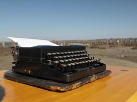 machine à écrire vintage sur une table en bois, faite à la main sur un fond de ciel bleu photo