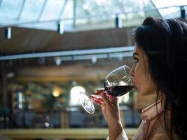 Portrait de modèle de fille brune buvant du vin rouge dans un verre photo