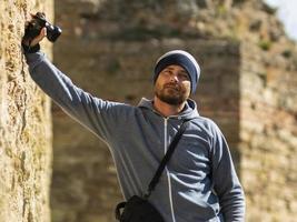 un homme barbu portant un chapeau tricoté se tient contre un mur dans une forteresse avec un appareil photo à la main et un sac photo sur son épaule