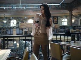 modèle de belle fille avec de longues jambes dans une jupe courte est debout avec un verre dans un restaurant photo