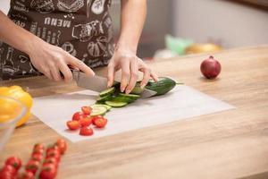 mains de femme couper le concombre, derrière les légumes frais. photo