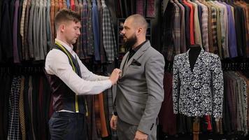 le couturier masculin mesurant le costume avec un ruban à mesurer sur un modèle masculin photo