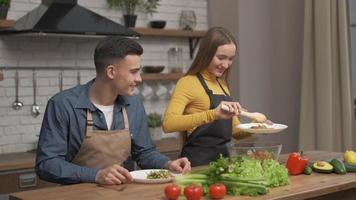 jolie fille met une salade de légumes sur l'assiette dans la cuisine. photo