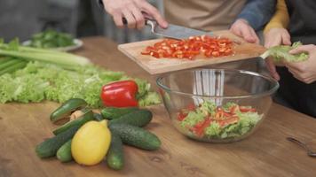 gros plan sur des mains d'homme coupant des légumes sur une planche à découper en bois pour la salade sur la table avec des aliments sains dans la cuisine. photo