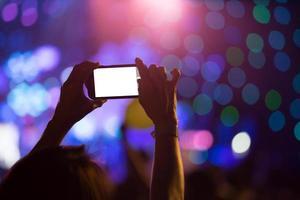 la main avec un smartphone enregistre une fête de luxe avec un écran blanc vierge photo