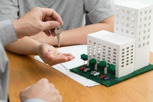 femmes prenant les clés de l'agent immobilier et discutant de l'hypothèque après la signature du contrat de location photo