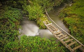 petite passerelle rurale traversant un ruisseau tordu photo