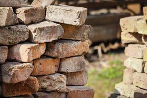 coin de mur de briques avec de vieilles briques rouges et de l'herbe visible sur l'arrière-plan photo