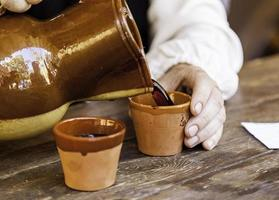 servir du vin dans un pot en argile photo