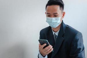 les hommes d'affaires portent des masques faciaux pour regarder leur téléphone portable photo