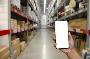 main tenant l'écran vierge de l'image de la maquette du téléphone pour le texte publicitaire dans l'entrepôt ou l'arrière-plan de stockage photo