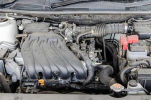 le moteur de la voiture est un moteur sale, des pièces automobiles, une accumulation de poussière. composants automobiles poussiéreux photo