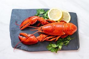 homard rouge aux légumes et citron sur plaque d'ardoise noire photo