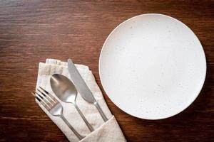 assiette ou plat vide avec couteau, fourchette et cuillère sur fond de carreaux de bois photo