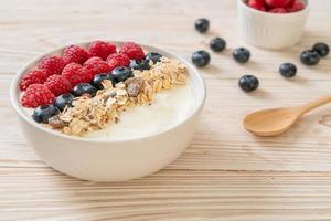 bol de yaourt fait maison avec framboise, myrtille et granola - style alimentaire sain photo