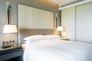 décoration d'oreillers blancs sur le lit à l'intérieur de la chambre photo