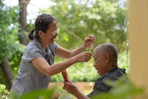 femme asiatique âgée faisant la coupe de cheveux à son mari à la maison patio photo