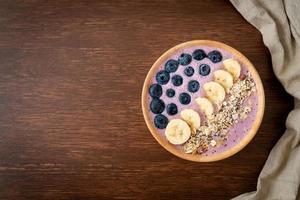bol de yaourt ou de smoothie avec myrtille, banane et granola - style alimentaire sain photo