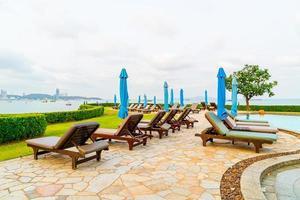 chaise piscine ou lit piscine et parasol autour de la piscine avec fond de plage de mer à pattaya en thaïlande photo
