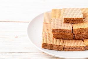 gaufrettes au chocolat avec crème au chocolat sur fond de bois photo