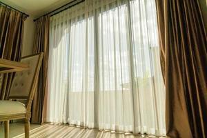 beau rideau avec la lumière du soleil de la fenêtre en verre photo