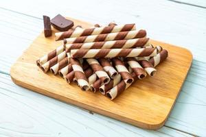Rouleau de bâton de gaufrettes au chocolat sur fond de bois photo