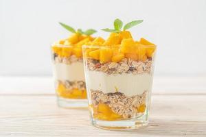 yaourt à la mangue fraîche avec granola en verre - style alimentaire sain photo