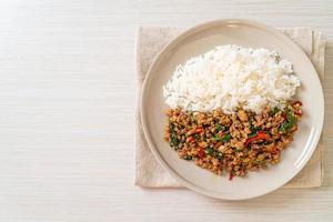 Basilic thaï sauté avec porc haché sur riz garni photo