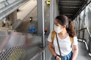 jeune femme asiatique au visage souriant et portant un masque facial comme ligne directrice en matière de distanciation sociale. elle utilise un escalator pour monter à la station de train aérien. nouveau mode de vie normal, covid-19, concept de coronavirus photo