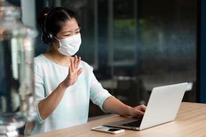 portrait d'une jeune femme asiatique portant un masque facial et des écouteurs et travaillant à distance à l'aide d'une conférence d'appel vidéo sur ordinateur dans un espace de coworking. distanciation sociale et nouveau concept de mode de vie normal photo