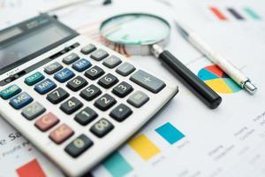 calculatrice sur tableau et feuille de calcul graphique. développement financier, compte bancaire, statistiques, économie de données de recherche analytique d'investissement, négociation en bourse, concept d'entreprise commerciale. photo