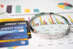 modèle de carte de crédit avec loupe, développement financier, comptabilité, statistiques, investissement, recherche analytique, données, économie, bureau, entreprise, banque, concept. photo