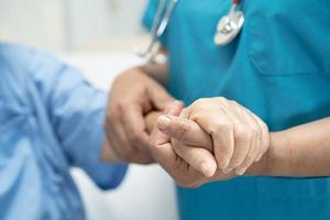 médecin tenant des mains touchantes femme âgée ou vieille dame asiatique patiente avec amour, soins, aide, encouragement et empathie à l'hôpital de soins infirmiers, concept médical fort et sain photo