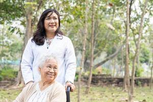 patiente asiatique âgée ou âgée avec soins, aide et soutien sur fauteuil roulant dans le parc en vacances, concept médical fort et sain. photo