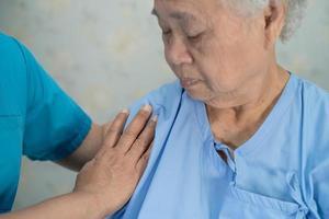infirmière asiatique physiothérapeute médecin touchant une patiente asiatique âgée ou âgée avec amour, soins, aide, encouragement et empathie à l'hôpital de soins infirmiers, concept médical solide et sain. photo