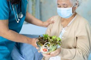 Une patiente asiatique âgée ou âgée de vieille dame mangeant un petit-déjeuner de légumes sains avec espoir et heureuse assise et affamée sur son lit à l'hôpital. photo