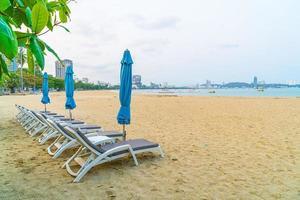 Chaises de plage avec parasols sur la plage de la mer à Pattaya en Thaïlande photo