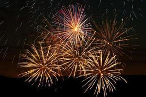 feux d'artifice lumineux lors d'une nuit de fête. lumières colorées dans le ciel sombre pour des vacances. photo