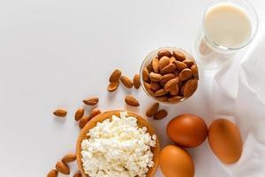 aliments protéinés sur fond blanc - fromage cottage, œufs, noix. un ensemble d'aliments sains pour une alimentation équilibrée. photo