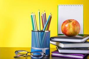 concept de retour à l'école. fournitures scolaires et livres sur fond jaune. place pour le texte. photo