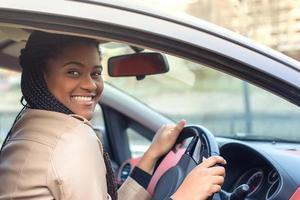 heureuse femme afro-américaine dans une voiture au volant, automne-hiver photo