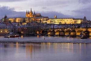 Nuit colorée de noël enneigé prague petite ville avec château gothique et pont charles, république tchèque photo