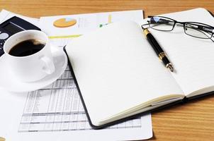 concept d'entreprise avec pages de livre vierges et verre et tasse à café et calculatrice avec document sur table de travail photo