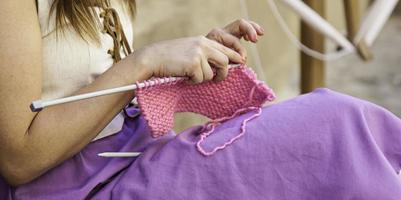 Jeune femme tricotant des vêtements en laine photo