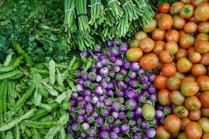 les haricots ailés, les aubergines violettes, les tomates, la gloire du matin et la coriandre se vendaient sur le marché photo