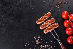 savoureuses saucisses fraîches grillées avec des légumes, des épices et des herbes photo