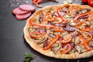 délicieuse pizza fraîche faite dans un four à sole avec des saucisses, du poivre et des tomates photo