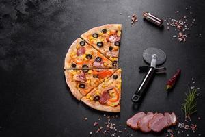 délicieuse pizza fraîche faite dans un four à sole avec des olives, du piment et du jambon photo
